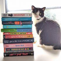 Stack of books that are reviewed next to a cat