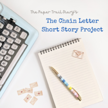 """A typewriter next to some mini envelopes and a notebook with a pen and paperclip on top with the heading """"The Paper Trail Diary's The Chain Letter Short Story Project."""""""