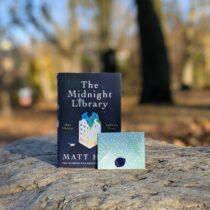 A book and small envelope stand on a rock. The blurred background is of a park with leaves on the ground.